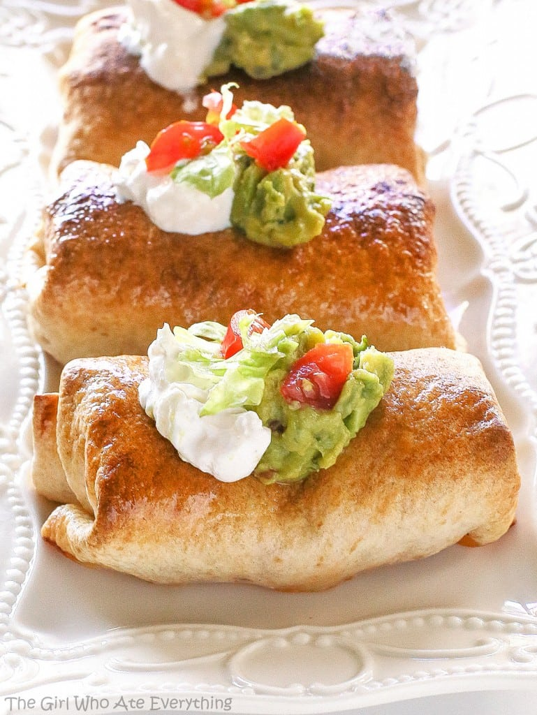 Baked Chicken Chimichangas with sour cream, guacamole, and tomato on a plate.