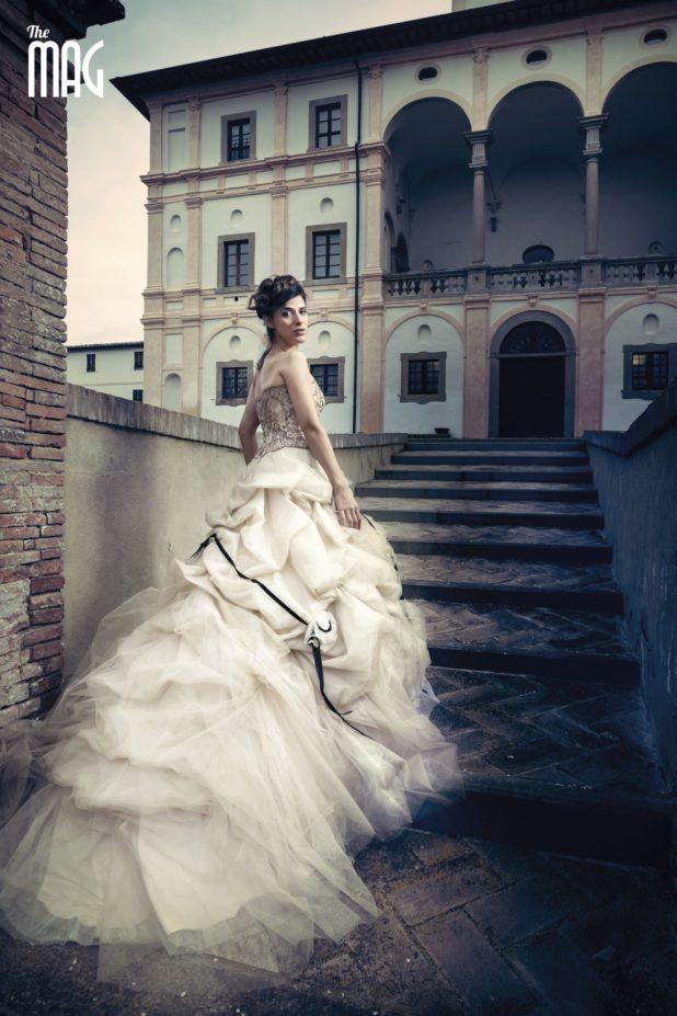 Fotografia di Lucia Rossi in abito da cerimonia mentre sale le scale a Villa Magherini Graziani