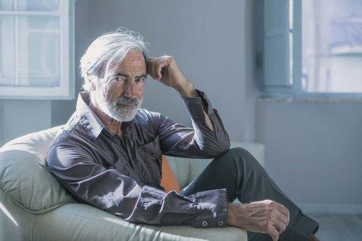 Foto di Massimo Gradini seduto nel divano della sua casa di Trestina