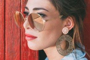 Primissimo piano di Monica Bartolucci con grandi orecchini e occhiali da sole