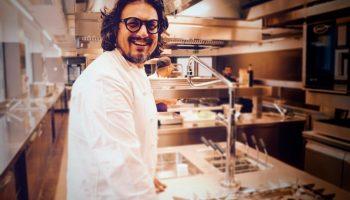 Alessandro Borghese sorridente mentre cucina