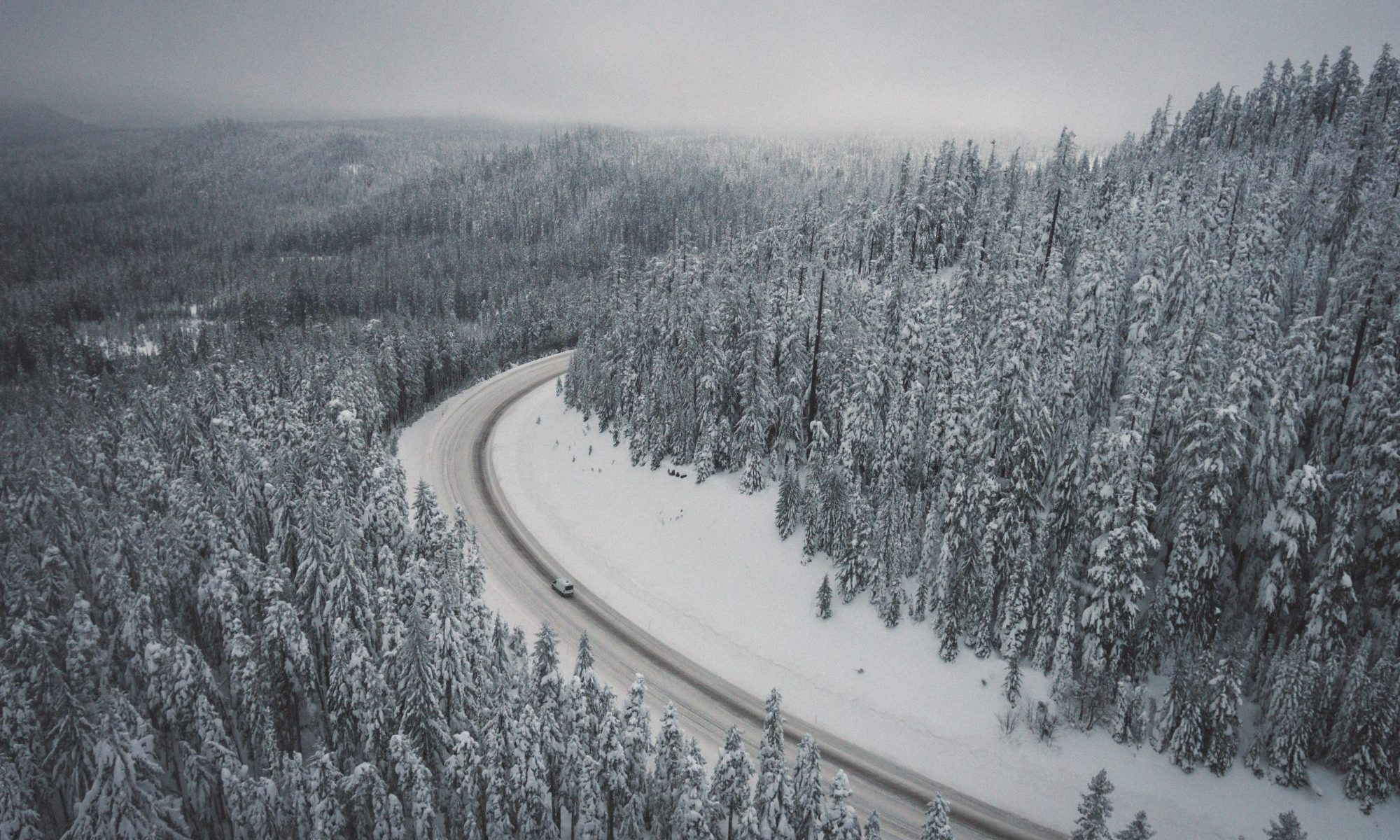 Driving with snow- check if you need snow tyres and/or snow chains. Photo Adrian- Unsplash. Skiers Face Winterisation and Ski Rack Charges Adding up to £179 On Car Hire Bill.