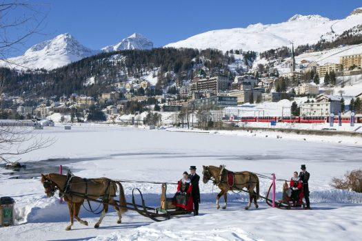 ENGADIN ST. MORITZ - The Schlitteda, an Engadin folk custom, by Lake St. Moritz. The women are dressed in Engadin Sunday costume. View of frozen Lake St. Moritz and of St. Moritz Dorf with Badrutt's Palace Hotel. In background the Piz Albana (3082m), Piz Gueglia (3192m) and the Corviglia ski area with the Piz Nair (3022m). Copyright by: ENGADIN St. Moritz By-line: swiss-image.ch/Christof Sonderegger