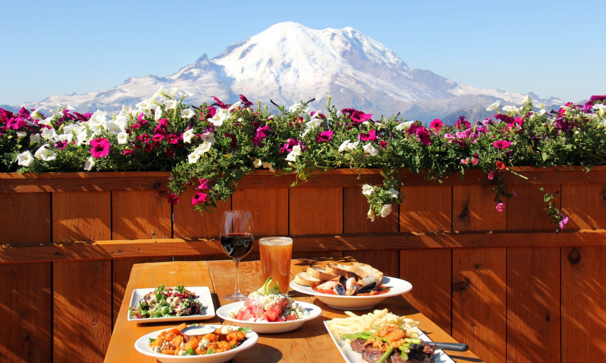 A table with a view of Mount Rainer- Crystal Mountain Resort in Washington state acquired by Alterra Mountain Company.