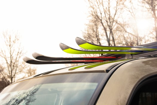 Two pairs of skis loaded into a ski rack on top of car. Heading out for a day of outdoor fun on the ski slopes.Photo: ICarhireinsurance.com - Skiers Over New Year Prepare for a £450 Wipeout at the Car Hire Rental Desk.