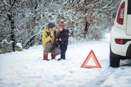 A woman with a child on the winter road. emergency sign. Skiers Face Winterisation and Ski Rack Charges Adding up to £179 On Car Hire Bill.  Photo: iCarhireinsurance.com