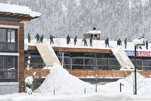 Soldiers cleaning up snow from a roof. Photo: Kerstin Joensson AP. Bundesheer. Two ski patrollers died in Morillon setting avalanche control charges.