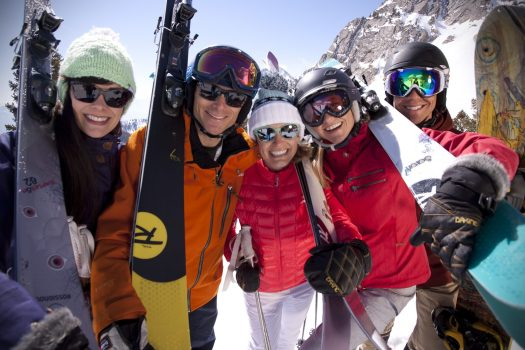 A group of friends skiers and boarders are all smiles - Top of John Paul Lift in Snowbasin. Photo: Chris Pearson. Ski Utah. Utah had its best Ski Season Ever in 2018-19