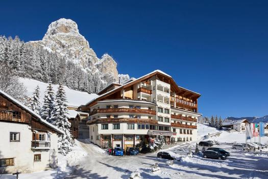 Exteior of the Hotel Sassongher in Alta Badia in winter. Book your stay at the Hotel Sassongher here. Plan your summer in the mountains of Alta Badia.