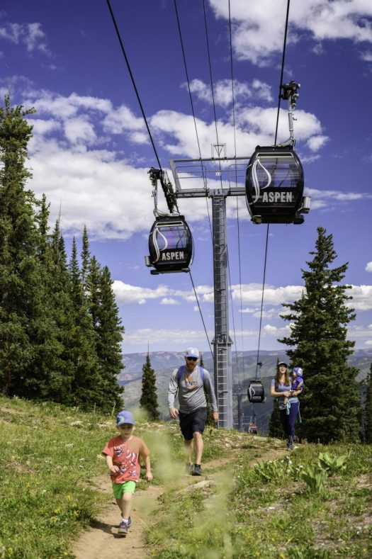 A family hiking under the Silver Queen Gondola in Aspen. Photo: Aspen Skiing Company. Aspen Snowmass is opening for the Summer Season.