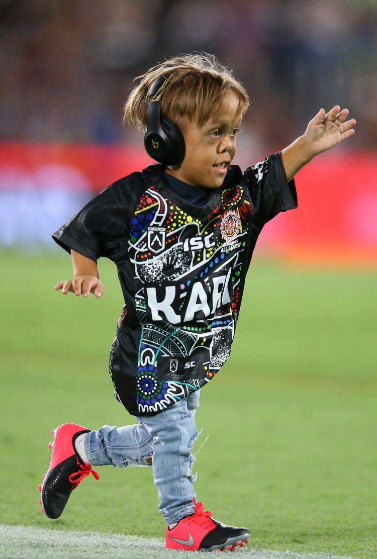 Um alegre Quaden usava uma camiseta preta e fones de ouvido com cancelamento de ruído enquanto liderava o time em campo enquanto uma multidão emocional observava