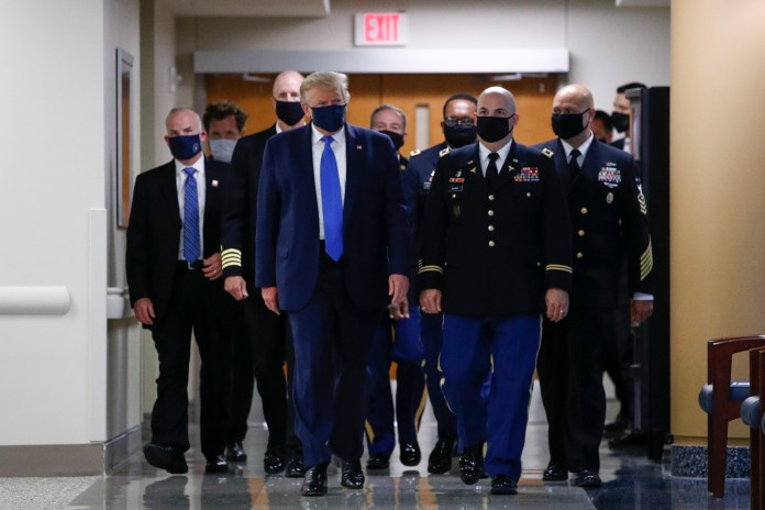 Trump, in the center, wears a mask during his visit to the Walter Reed National Military Medical Center in Bethesda, Maryland, July 11, 2020