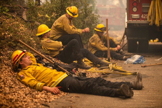 Firefighters rest in a smoldering forest in the Cascadel Woods