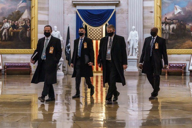 Security officials survey the Capitol on Monday