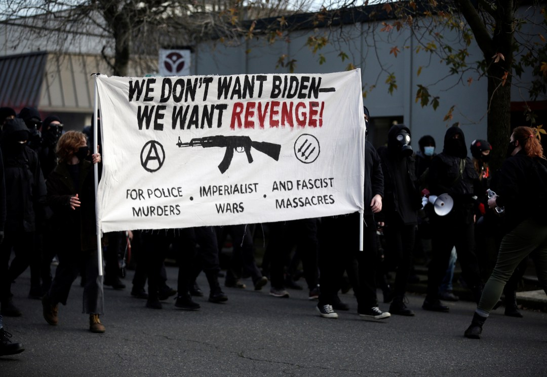 Antifa supported pictured marching in Oregon with signs saying 'We don't want Joe Biden, we want revenge'