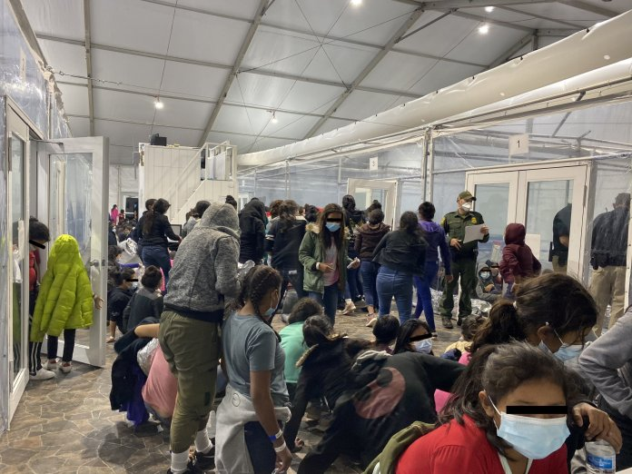 Migrants crowd a room with walls of plastic sheeting at the U.S. Customs and Border Protection temporary processing center in Donna, Texas