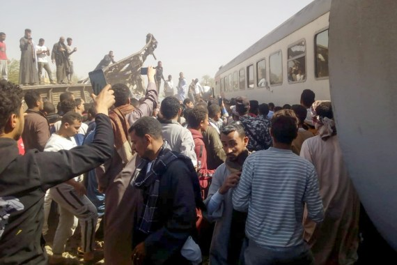 People inspect the damage after two trains have collided near the city of Sohag, Egypt, March 26