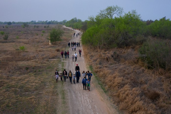 Migrants walking  towards the border wall after crossing the Rio Grande river