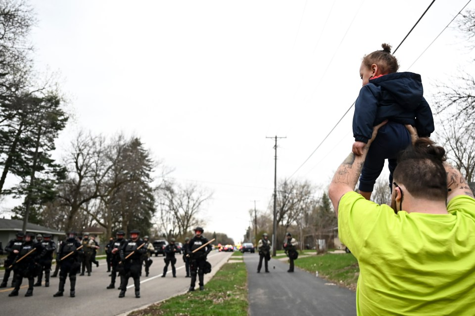 Daunte' brother, Damik, holding his son, Daunte Wright Jr. in front of officers