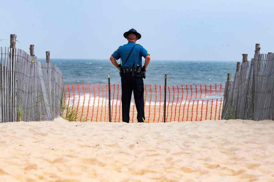A Delaware State Trooper stands guard on the beach as US President Joe Biden arrives on Marine One
