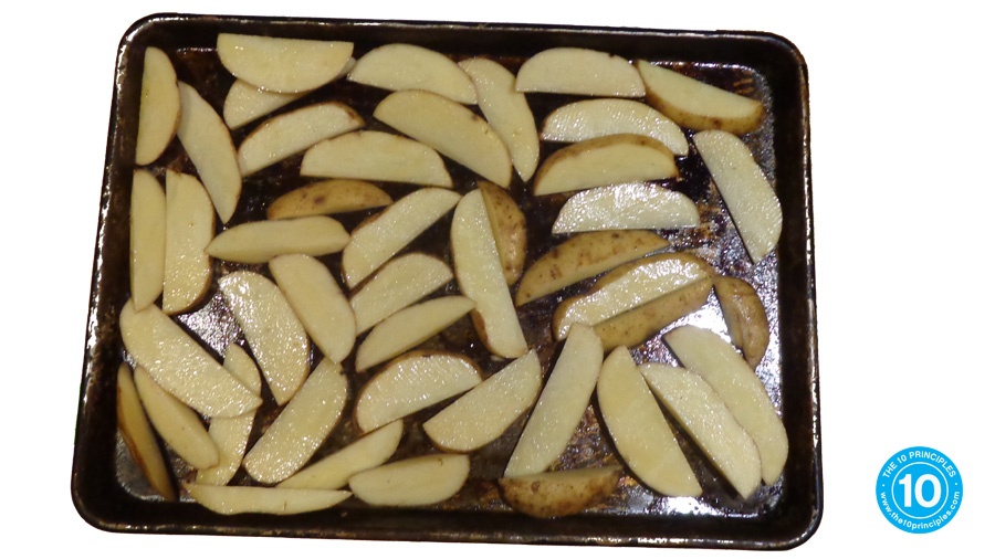 Take the hot tray out of the oven and empty the French soon-to-be-fried potatoes onto the tray