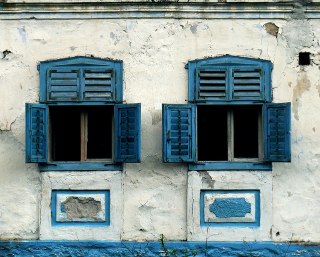 Two open windows in the wall of an old building