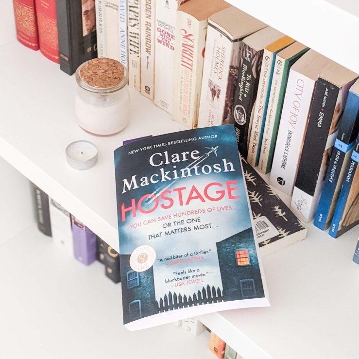 Hostage by Clare Mackintosh -- book lying on a white bookshelf beside books