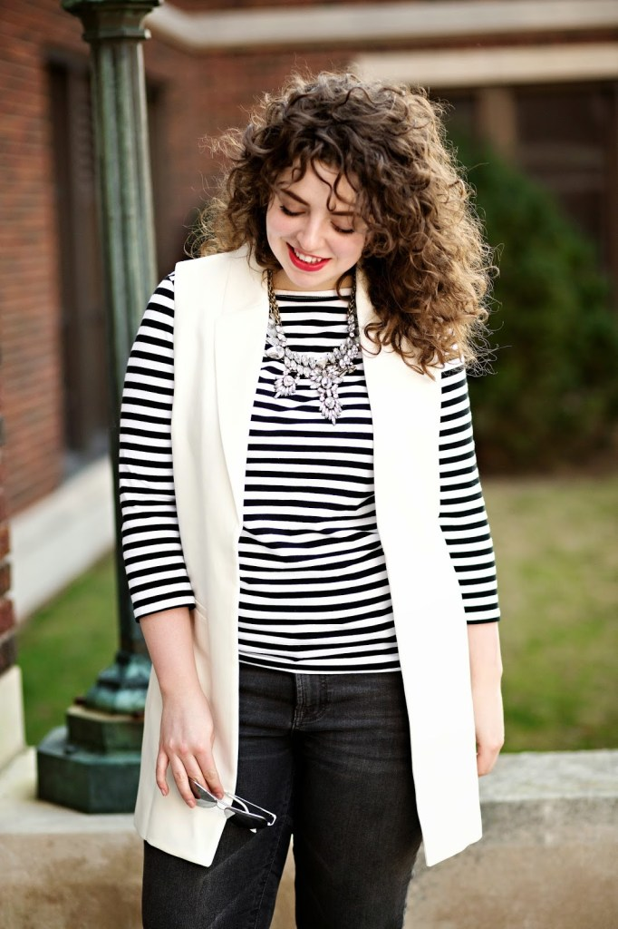 Black and white classic outfit with the current trend of a white, long vest! Paired with silver loafers and a statement necklace.