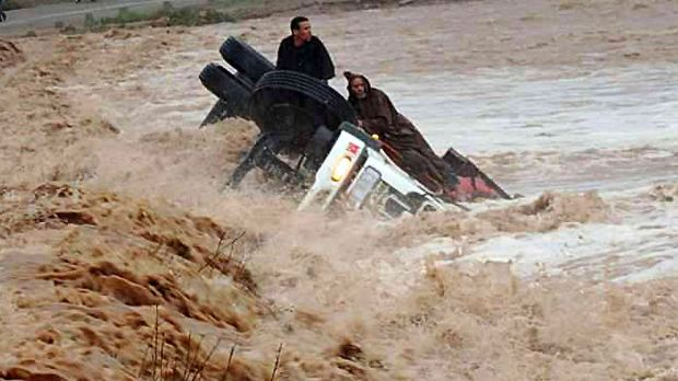 Clinging to life: Driver and passenger sit on a truck stranded in flood waters in the southern region of Ouarzazate in Morocco.