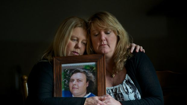 Tracey Downward and Julie Nestic hold a photo of their brother, Adam White.