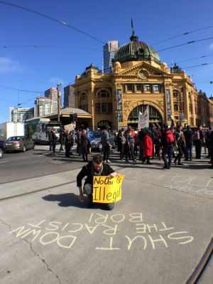 Protesters stop traffic outside Flinders Street during action against Operation Border Force.