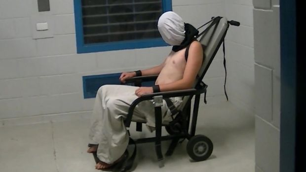 Dylan Voller is hooded an strapped into a restraining chair in the <i>Four Corners</i> footage.