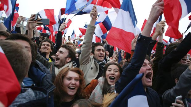 Supporters of Emmanuel Macron kiss as celebrate outside the Louvre museum in Paris.