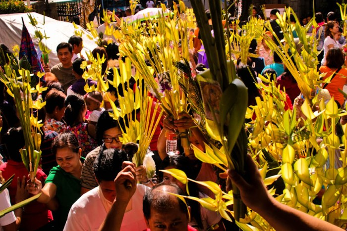 Churchgoers wave to the air their palaspas as a priest blesses the fronds with holy water before the start of the Palm Sunday mass at the Holy Cross Parish in Makati City. Photo by: Chris Quintana