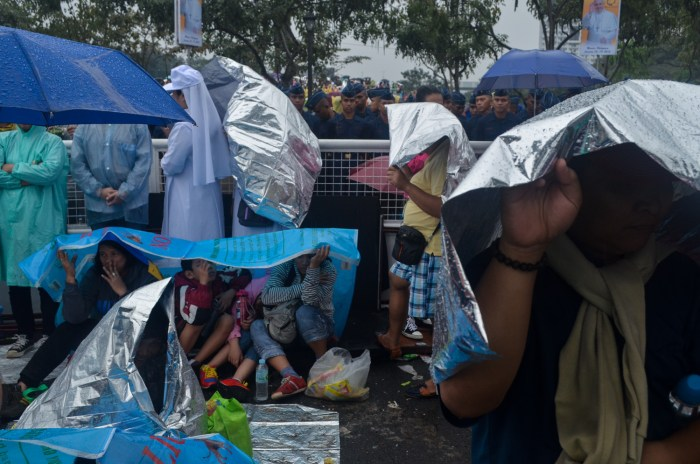 The crowd use makeshift shades and raincoats while waiting for the Holy Father. Photo by: Bart Manoguid