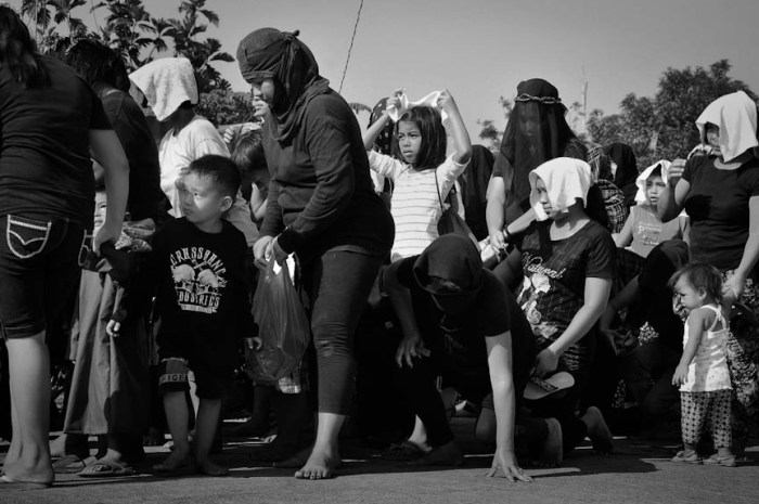On barefoot, the women penitents are joined by young ones before they begin their walk. Initially the group kneels to pray the rosary. As they pray the first mystery of the rosary, the group starts their walk with the male penitents in front. Photo by: Dax Simbol