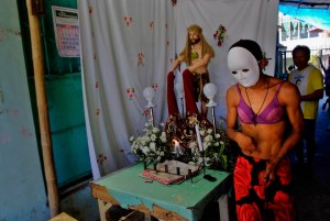 A flagellant wearing a bra and white mask exits a prayer altar along the streets of Kalayaan, Laguna. Photo by: Sonny Yabao