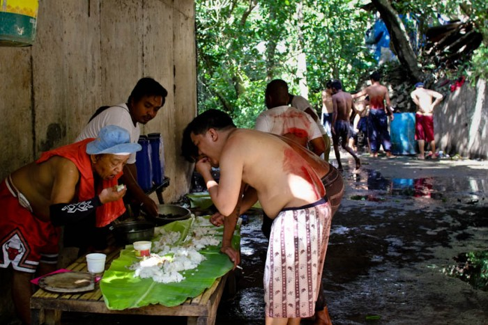 Members of Hugas Dugo share a meal under the bridge as others still wash up in the background in Pakil, Laguna. Photo by: Chris Quintana