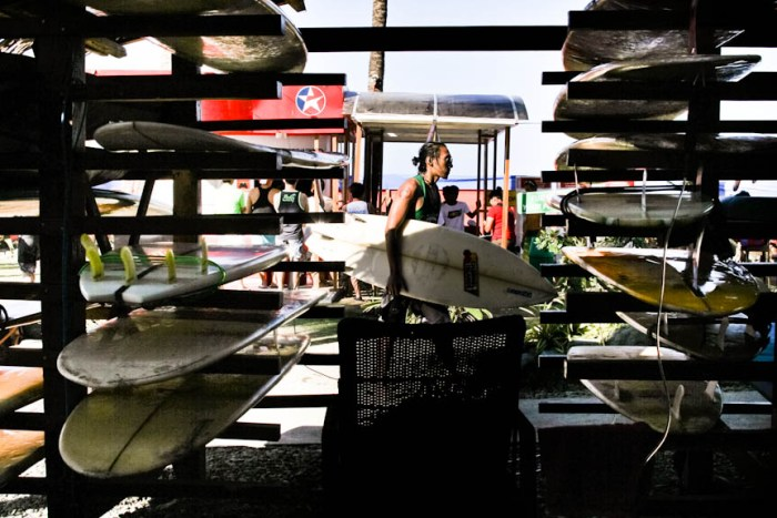 A surfer passes by a stack surfboards inside the Nalu Surf Camp in Baler, Aurora. Photo by: Chris Quintana
