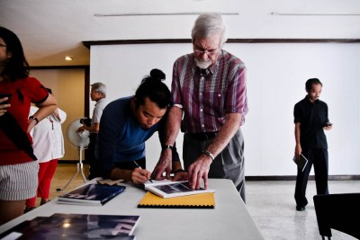 Peter Wallace, a writer, gets his copy signed by Manix Abrera during the opening of his exhibit at the U.P. Vargas Museum. Photo by: Kimmy Baraoidan