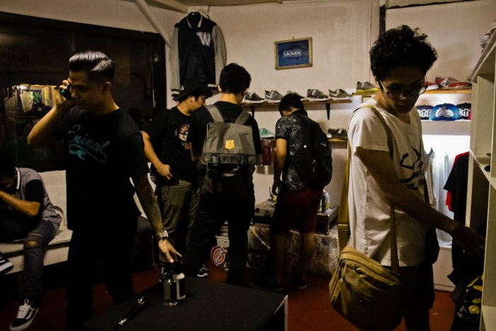 Ajok Jacobe (far left), owner of clothing brand Enimal and co-owner of Fam, talks on the phone while customers check out the store's merchandise in Los Baños, Laguna. (Photo by: Kimmy Baraoidan)