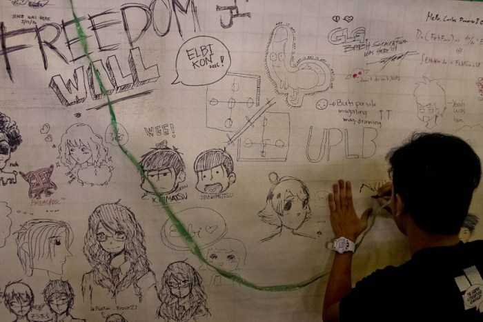 An attendee writes on the Freedom Wall during Elbikon 2016 in UPLB. (Photo by: Kimmy Baraoidan)