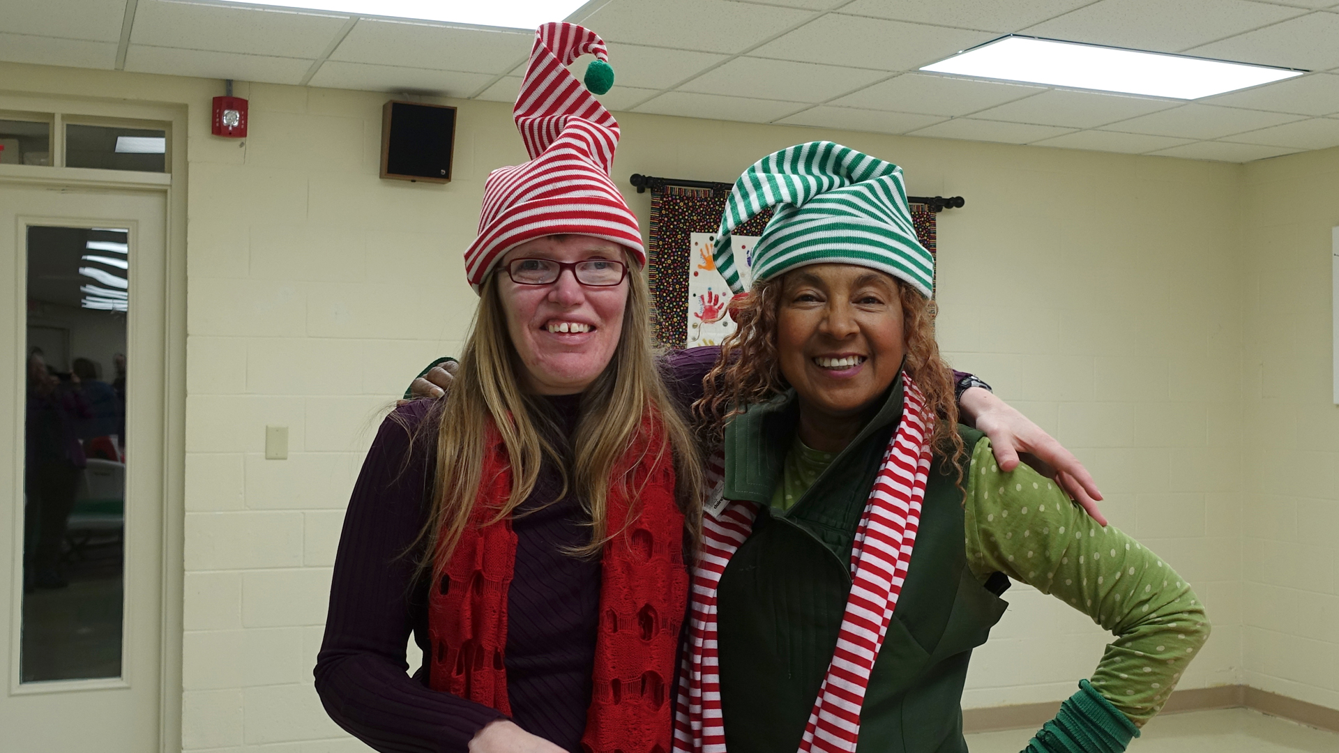 Jessica and Sonya in red and green striped Christmas hats, smile for the camera