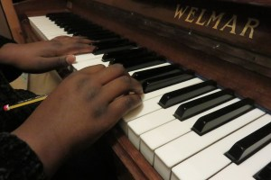 A close up photo of one of our piano students playing the piano.