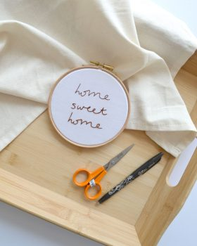 Home sweet home embroidery pattern laid on top of a wooden tray and cream fabric. Scissors and a Frixion pen is next to the finished embroidery hoop.