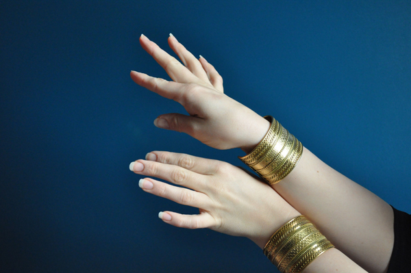 the artyologist- image of hands and brass jewelry in the style of vintage vogue 1939 cover