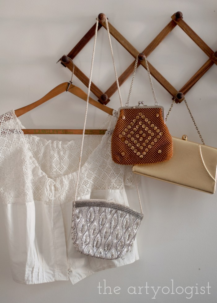 a wooden pegrack with vintage purses and a lace blouse hanging on it