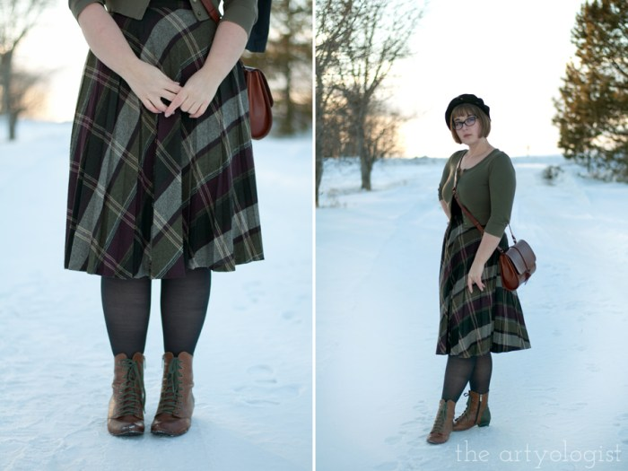 a lady wearing a vintage plaid skirt and green sweater with a vintage styled purse and beret in the snow