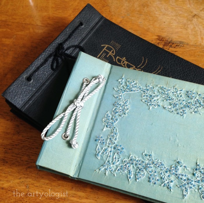 two vintage photo albums- one black with vintage writing and one mint blue with a beaded applique on the front cover