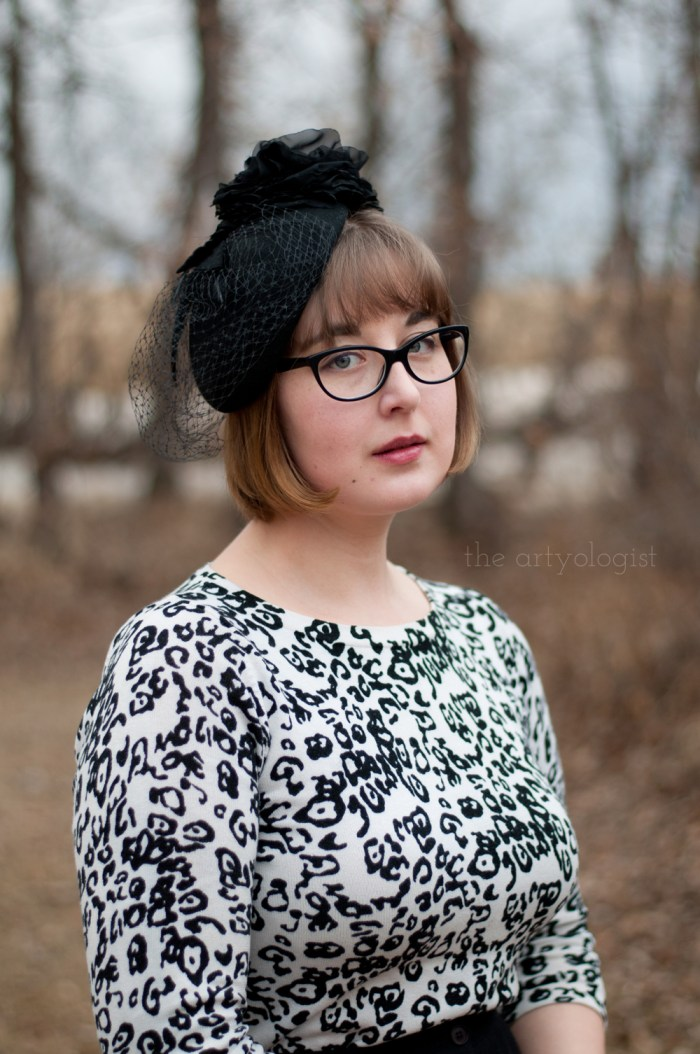 a woman wearing a white and black leopard printed sweater and a black wool fascinator hat with a flower